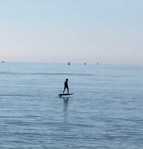 man on electric surfboard at sandbanks beach